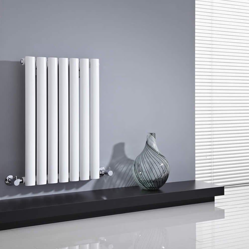 termosifone design bianco su parete grigia scura, mensola nera e vaso moderno.