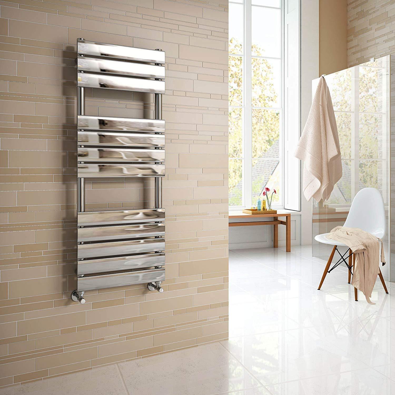 Bagno con radiatore cromato verticale su parete con mattonelle beige.