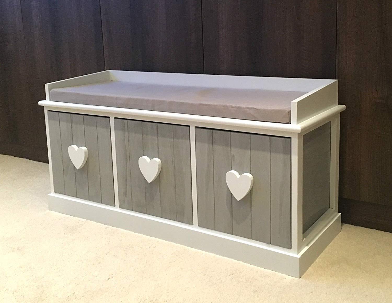 Cassapanca shabby con seduta, 3 sportelli in legno grigio e pomelli bianchi a forma di cuore.